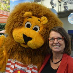Die hessische Umweltministerin Priska Hinz mit dem hessischen Maskottchen Qualileo in der Hessenhalle (Foto: HMUKLV)