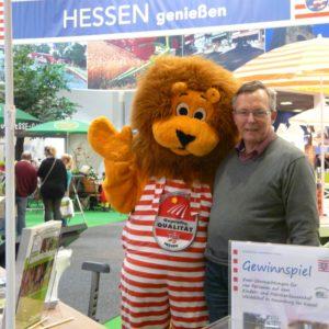 LLH-Direktor Andreas Sandhäger am Infostand mit dem Maskottchen Qualileo der Marketinggesellschaft Hessen