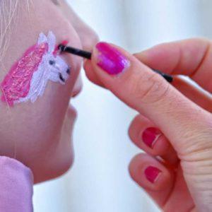 Hand mit Schminkpinsel beim Schminken eines Einhornmotives auf einer Mädchenwange