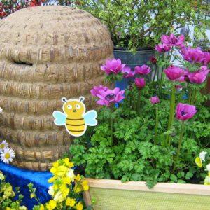 Bienenkorb mit Frühjahrsblühern und Steckbienen