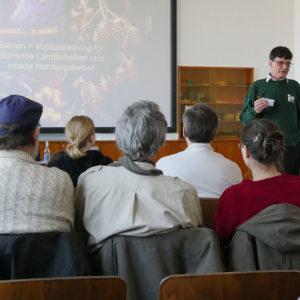 Vortragender mit Powerpoint Präsentation, im Vordergrund das Publikum
