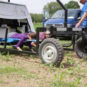 Zwei Personen auf einem Jäteflieger, der über ein Maisfeld fährt
