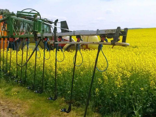 Pflanzenschutzspritze mit Dropleg-Technologie auf einem blühenden Rapsfeld