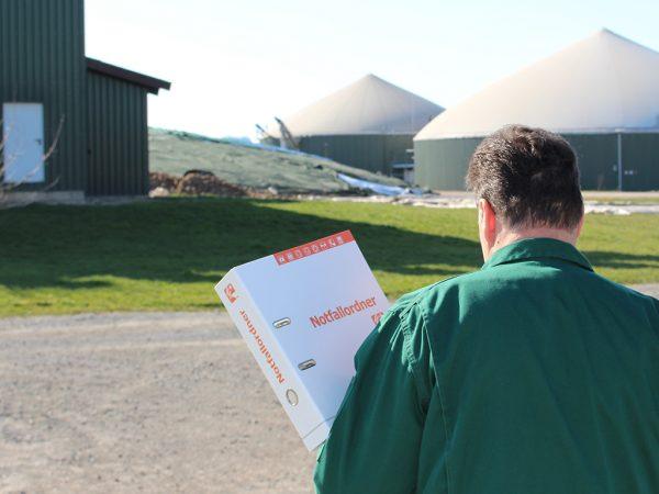 Mann mit Notfallordner in der Hand, im Hintergrund eine Biogasanlage
