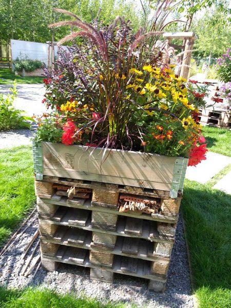 Palettenhochbeet mit Aufsatzrahmen; zwischen den Paletten ist ein Insektenhotel integriert