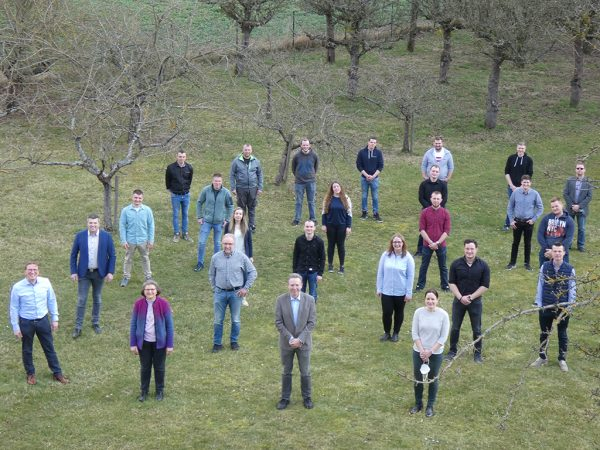 Personengruppe auf Wiese, im Hintergrund kahle Obstbäume