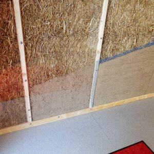 Die Seitenwand innen zeigt den Aufbau des Lehmputzes auf dem Stroh in verschiedenen Schichten