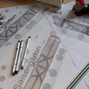 verschiedene Entwurfsskizzen auf Papier, in der Mitte Stifte, am Rand zwei Gartenzwergfiguren