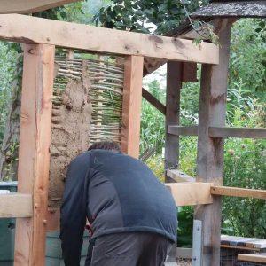 Dieser Teilnehmer versucht sich am Weidengeflecht mit Lehmbewurf als Ausfachung. Das geht überraschend schnell und einfach