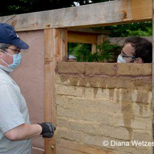 Zwei Teilnehmer arbeiten an der Ziegelausfachung im Fachwerkmodell