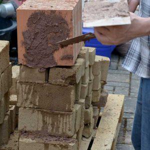 Der Seminarleiter zeigt an einem modernen Keramik-Dämmziegel, dass Lehmputze auch im Innenausbau von Neubauten sinnvoll und machbar sind